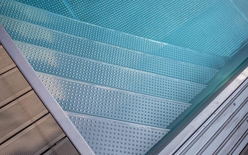 Detail nerezového schodiště u zapuštěného bazénu Imaginox na zahradě
