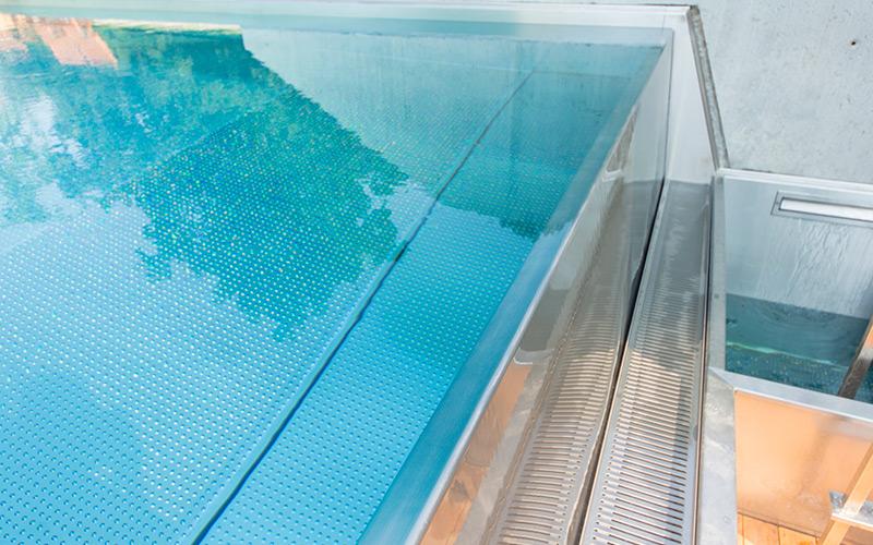 Detail přelivného bazénu Imaginox se žlabem umístěným pod úrovní lemu bazénu
